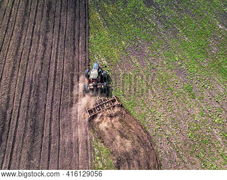 Agriculture Machine Harvesting Crop In Fields. Tractor Pulls Mechanism For Haymaking. Harvesting In