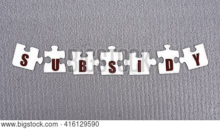 Subsidy - Word Composed Of Paper White Puzzles On A Gray Background. Business Concept