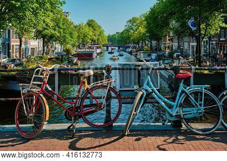 Amsterdam canal with boats and bicycles on a bridge