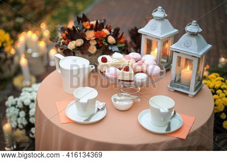 Cakes, tea, candles and flowers. Oudoor still life. Shallow depth of field.