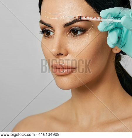 Botulinum Toxin Injections In A Womans Forehead For Blocking Mimic Wrinkles. Beautiful Face With Arr