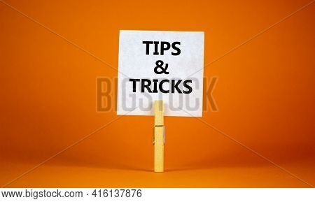 Tips And Tricks Symbol. White Paper On Wooden Clothespin. Words 'tips And Tricks'. Beautiful Orange