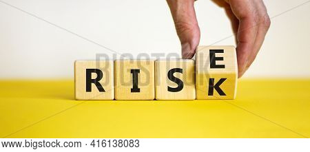 Risk Vs Rise Symbol. Businessman Turns A Wooden Cube And Changes The Word Risk To Rise. Beautiful Ye