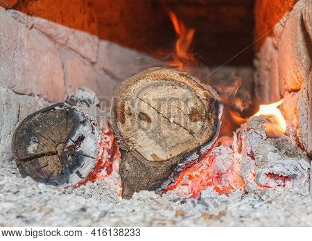 Round Wooden Logs Burn In The Stove. Eco-friendly Heating. Close-up. Selective Focus.