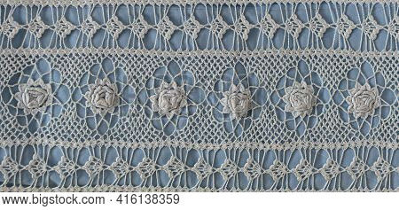 A Fragment Of A Wide Lace Insert Contains Small White Roses. Vintage Lace Crochet From Cotton Thread