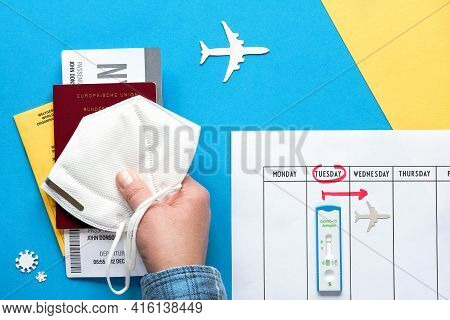 New Normal Travel During Covid-19 Restrictions, Flat Lay On Blue Yellow Paper. Hand Hold German Pass