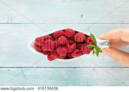 Fruity Raspberries In A Saucer Hold By A Woman Hand