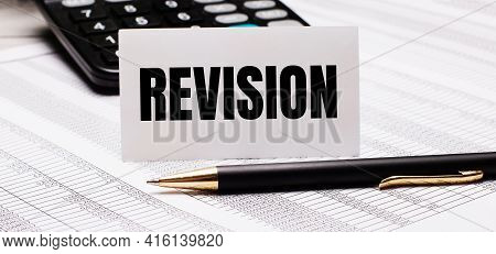 On The Table There Are Reports, A Pen, A Calculator And A White Card With The Text Revision. Defocus