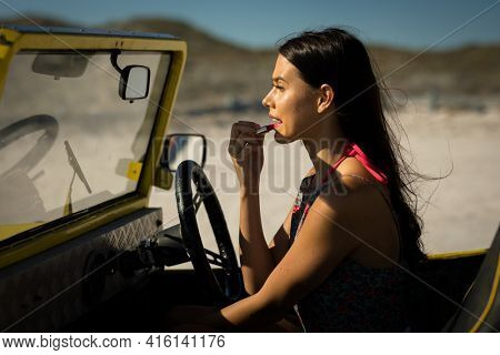 Happy caucasian woman sitting in beach buggy by the sea putting on lipstick. beach break on summer holiday road trip.