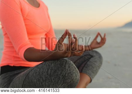 Middle section of mixed race woman on beach practicing yoga meditating. healthy outdoor leisure time by the sea.