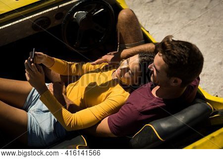Caucasian couple on a beach buggy by the sea using smartphone. beach break on summer holiday road trip.