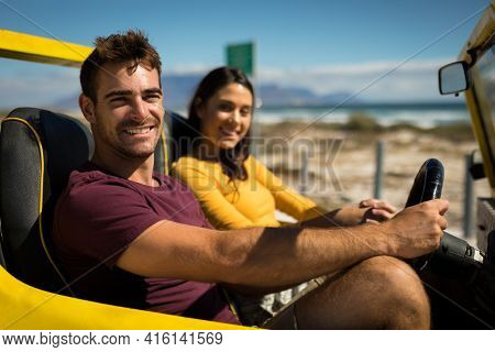 Portraits of happy caucasian couple looking to camera sitting in beach buggy by the sea talking. beach break on summer holiday road trip.