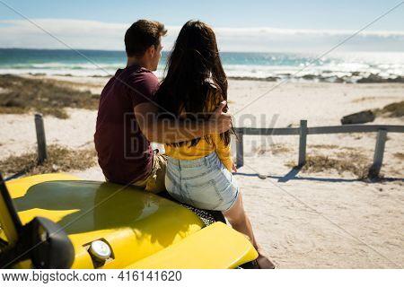 Happy caucasian couple sitting in beach buggy looking towards sea. beach break on summer holiday road trip.