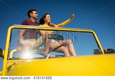 Happy caucasian couple sitting in beach buggy by the sea taking selfie. beach break on summer holiday road trip.