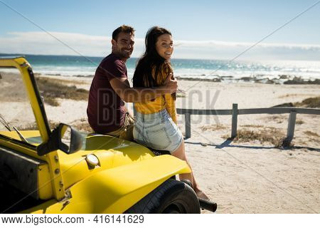 Happy caucasian couple sitting in beach buggy looking to camera. beach break on summer holiday road trip.
