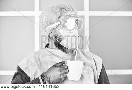 Medical Mask As Corona Protection. Man Drink Coffee In Respirator Protective Mask. Coronavirus Pande