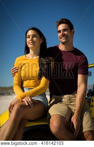 Happy caucasian couple woman sitting in beach buggy by the sea both looking ahead. beach break on summer holiday road trip.