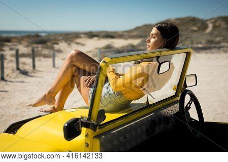 Caucasian woman lying on a beach buggy looking towards sea. beach break on summer holiday road trip.