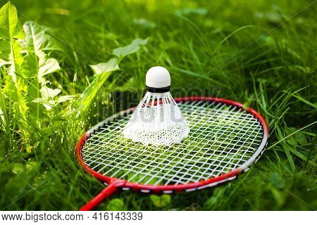 Shuttlecock And Badminton Racket Lie On The Green Grass. Summer Sunny Day. Concept Healthy Lifestyle