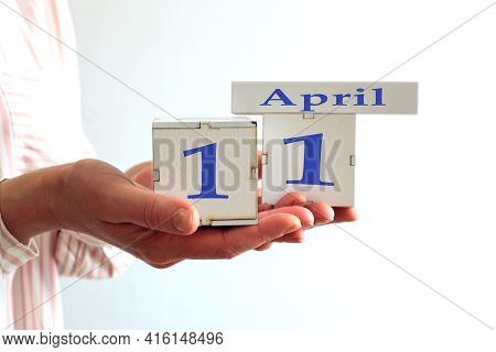 Calendar For April 11 : Women's Hands Hold Cubes With The Number 11, The Name Of The Month Of April