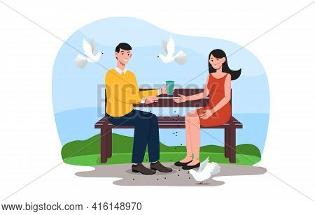 Young Couple Is Sitting On A Bench In Park And Feeding Pigeons. Man And Woman Scatter Feed For Urban