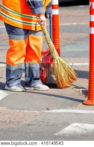 A Female Janitor In Bright Orange Uniforms Sweeps The Street By A Fence Of Orange Road Columns. Vert