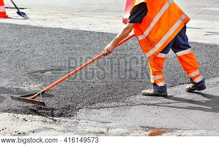 A Road Worker In A Bright Orange Overalls Renews A Section Of The Road With Fresh Hot Asphalt And Le