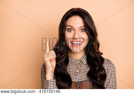 Portrait Of Pretty Cheerful Amazed Wavy-haired Girl Pointing Up Genius Idea Isolated Over Beige Past