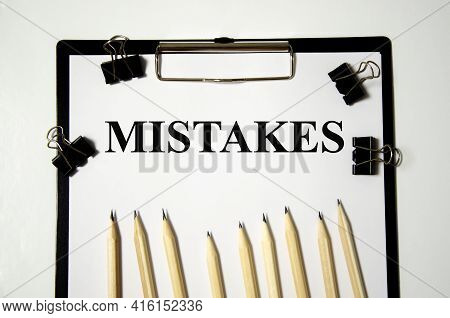 The Word Mistake The Word Is Written On A White Piece Of Paper With Pencils. Word