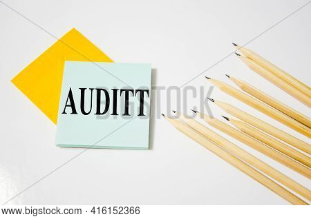 The Word Audit Word Written On A Yellow Piece Of Paper And White Background With Pencils Lying Next