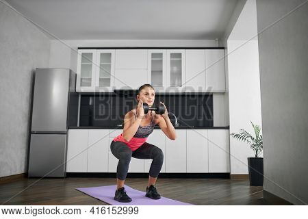 Side View Of Fit Caucasian Young Woman Squatting In Kitchen. Strong Girl Wearing Sportswear Training
