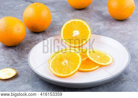 Pieces Of Fresh Orange On A Plate On The Table. Vitamins, Diet And Vigor