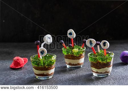 Multi-layered Dessert Of Chocolate Chip Cookies, Yoghurt And Green Jelly In Glass Glasses, Decorated