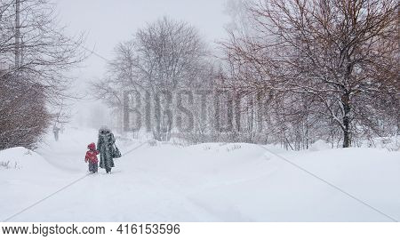 Snow Storm. Snowstorm On A Winter Day, Trees, Woman, Child, Go On The Road. Russia