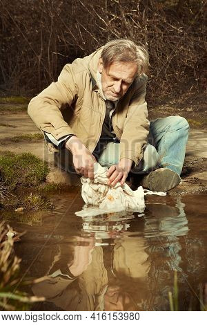 Older Homeless Man Washing His Clothes In Outdoor Water