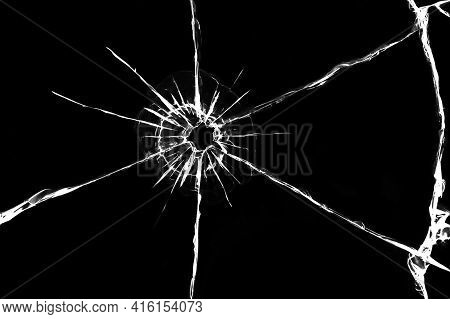 Texture Of Cracks On The Glass From The Shot. Cracked Glass For Design. Cracks On A Black Background