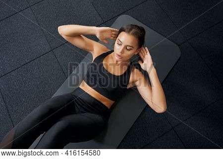 Above View Of Brunette Young Woman In Black Sportswear Doing Abs Exercise Workout On Black Mat. Conc
