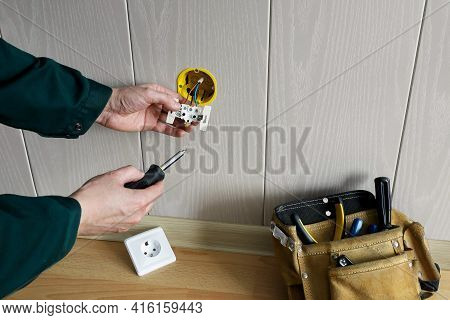 Electrician's Hands Installing Built-in Socket In Wall And Bag With Tools Located On Floor With Copy