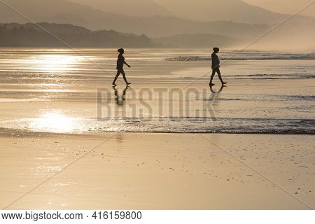 Matapalo, Costa Rica - 31/12/2013: Yellow Sunrise On Silhouettes People Walking On The Beach Early I