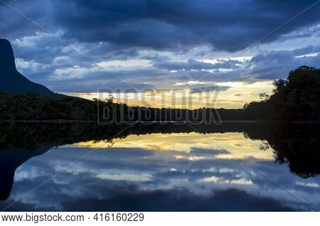 Sunset On The Auyantepui Mountain In The Canaima National Park And Its Reflection In The Water Of Th