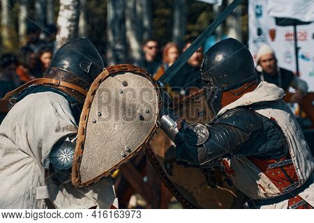 Battle Of Knights In Armor With Swords. Arena For Battles. Festival Of Historical Clubs In The Park.