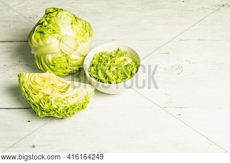Fresh Young Shredded Cabbage, Whole Head And Cut Piece On White Wooden Background