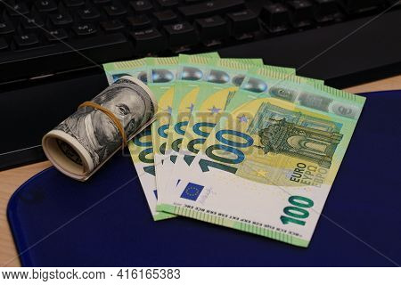 One Hundred Euro Bills And A Roll Of One Hundred Dollar Fanned Out On A Computer Keyboard. Close Up.