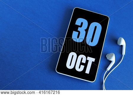 October 30. 30 St Day Of The Month, Calendar Date. Smartphone And White Headphones On A Blue Backgro
