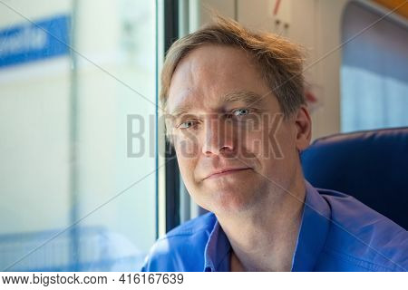 Caucasian Man In Forties With Blue Shirt On Commuter Train, Smiling