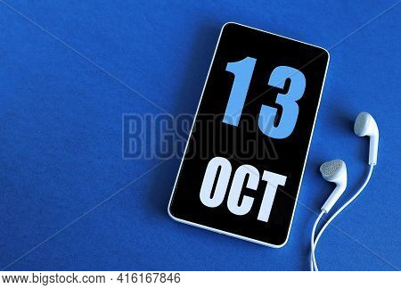 October 13. 13 St Day Of The Month, Calendar Date. Smartphone And White Headphones On A Blue Backgro