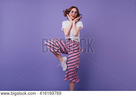 Good-humoured Curly Lady In Glasses Expressing Positive Emotions. Indoor Photo Of Slim Glad Woman In