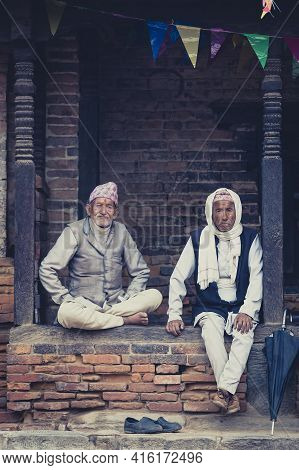 Bhaktapur, Nepal, April 23: Two Senior Nepalese Men Sitting And Resting Outside In The Old City Of B