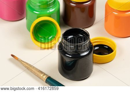Open Gouache Paint Glass With Other Tubes In The Background