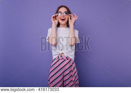 Smiling Joyful Girl Touching Her Sunglasses While Posing On Purple Background. Good-humoured Female